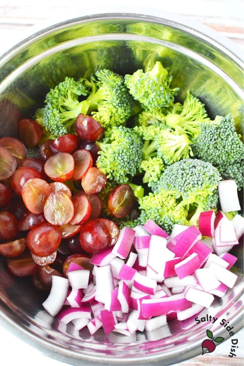 broccoli florets, grapes and red onions in a bowl