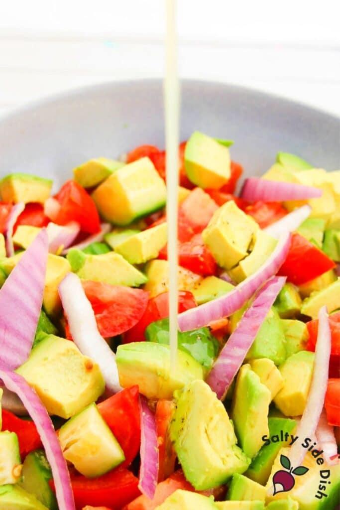 dressing pouring onto avocado salad