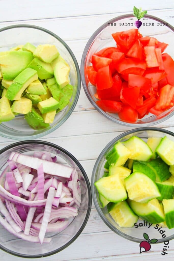 chopped avocados, ripe tomatoes, fresh cucumbers and red onions in prep bowls