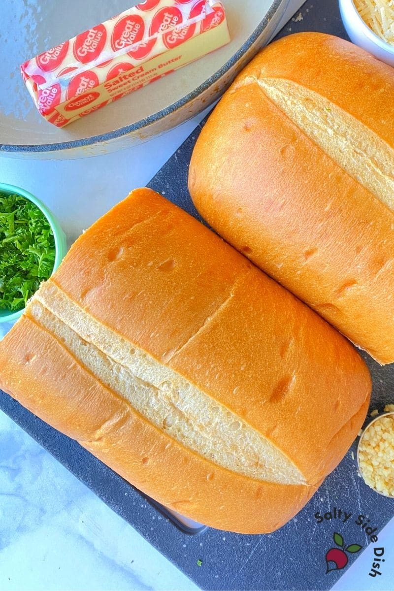 Garlic Parmesan Bread ingredients sitting on a table with butter, herbs, bread and cheese