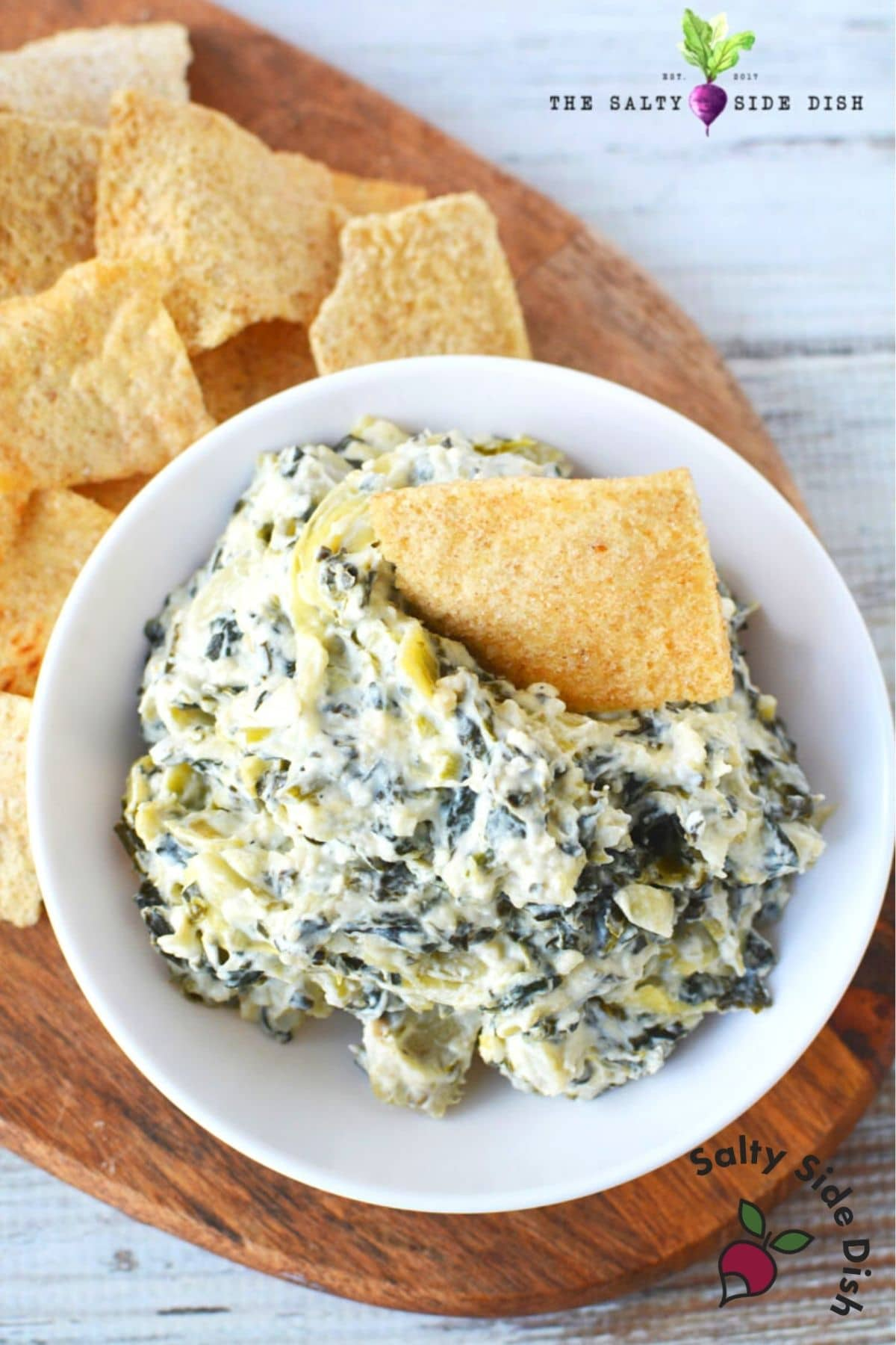 slow cooker spinach dip recipe in a serving bowl with pita chips