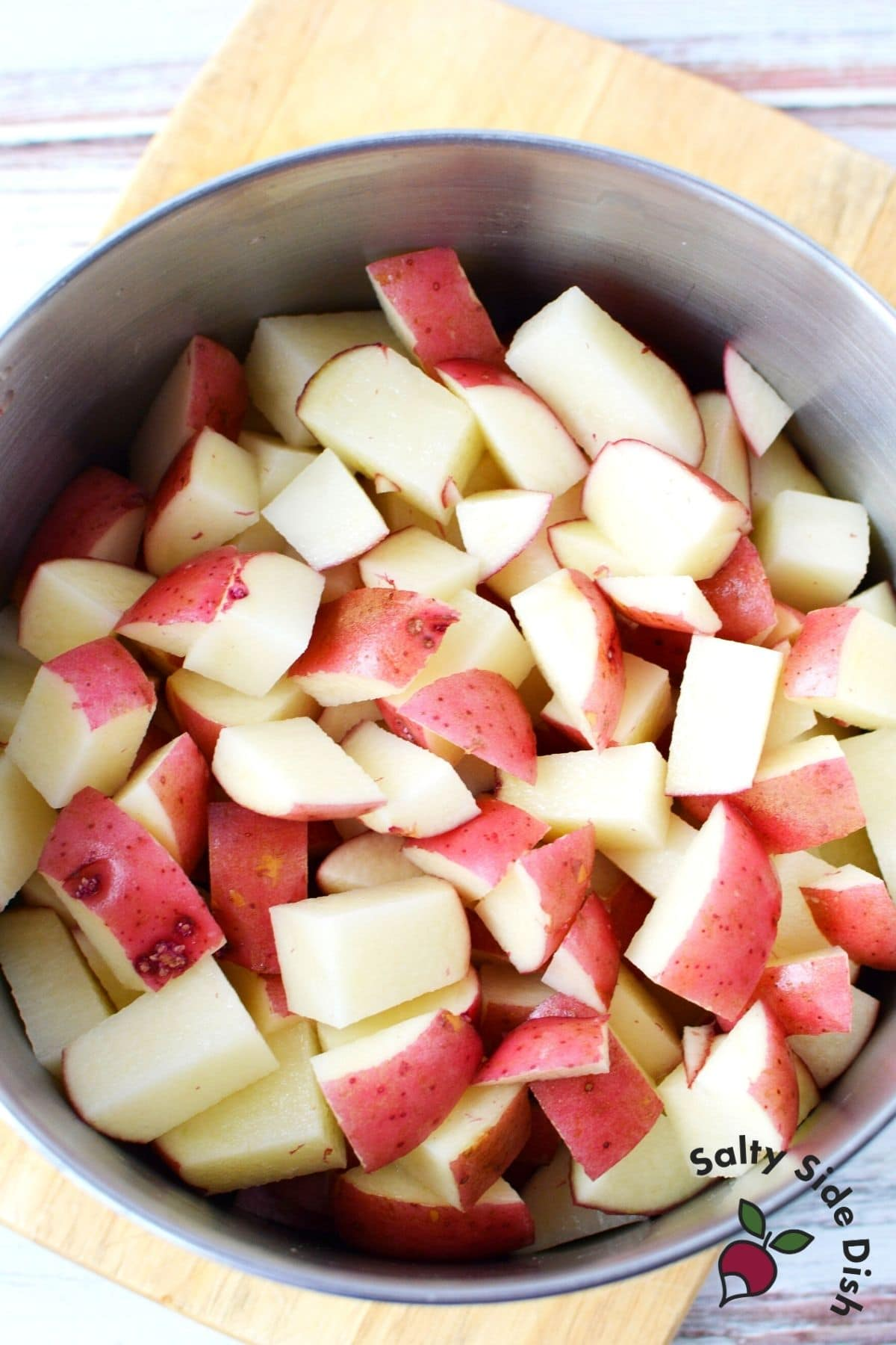 prepping boiled red potatoes in a pot