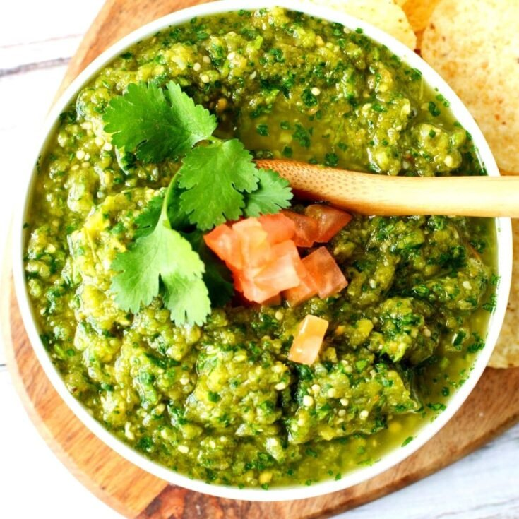 bowl of salsa verde with tomatoes and serving spoon