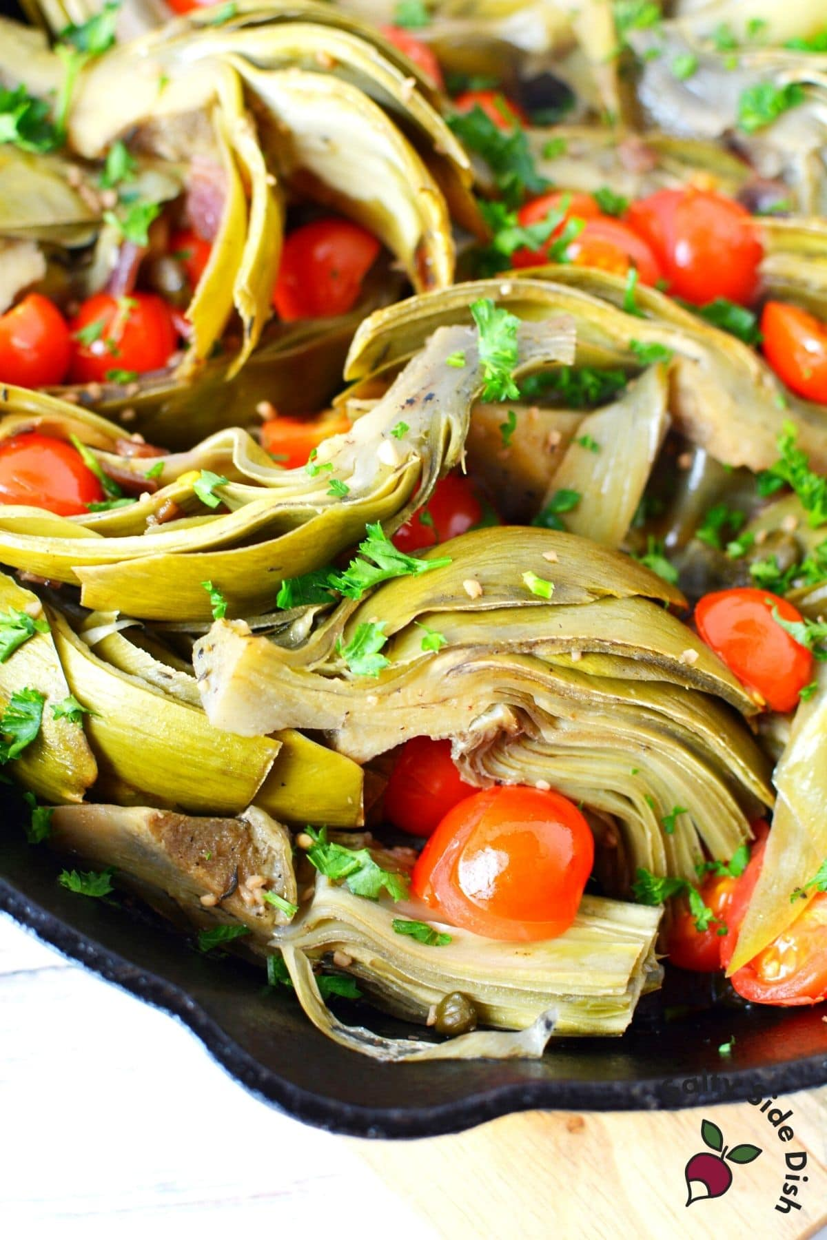 braised artichokes warm side dish in a cast iron skillet