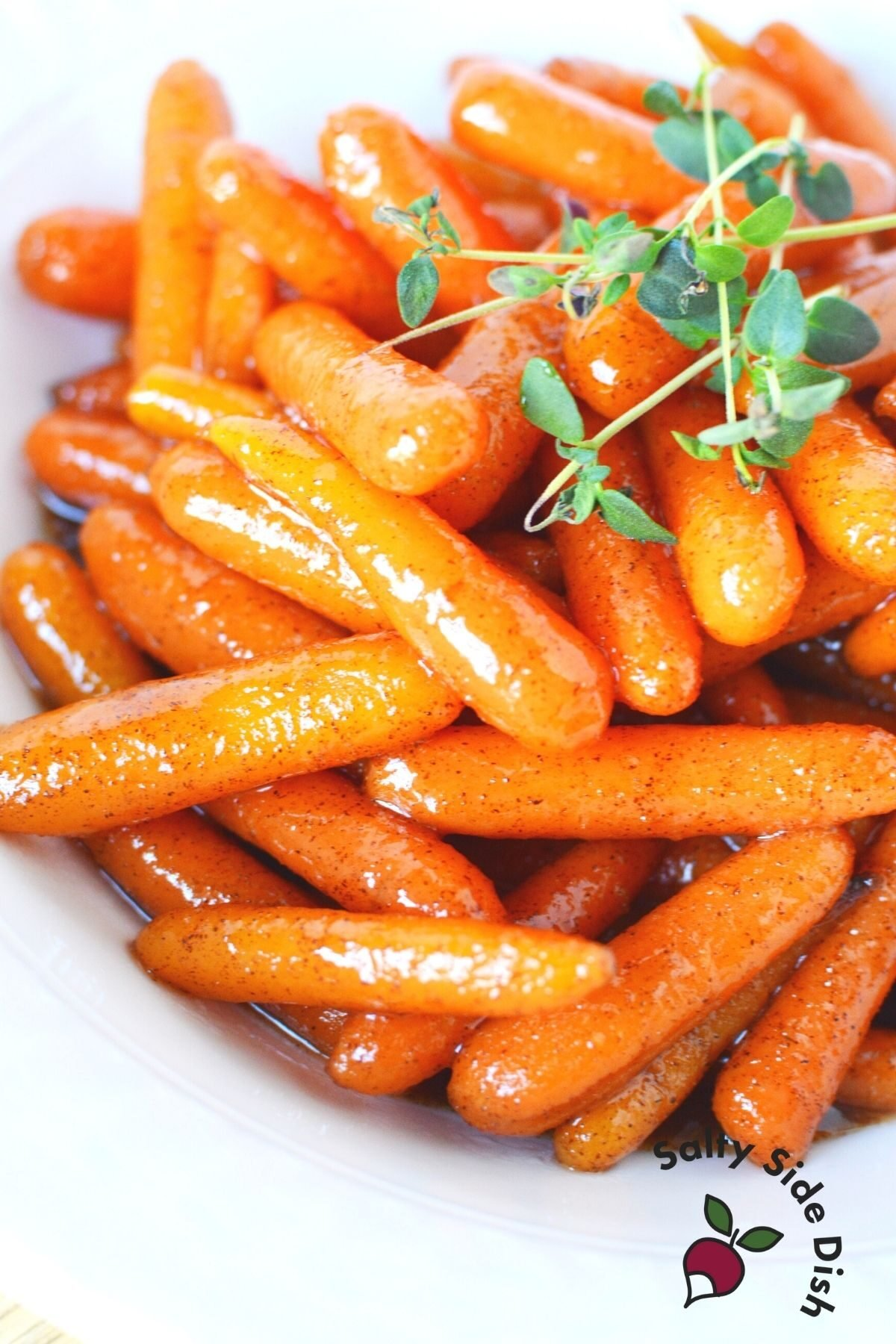 Cinnamon brown sugar glazed carrots on a white plate with herbs on top.