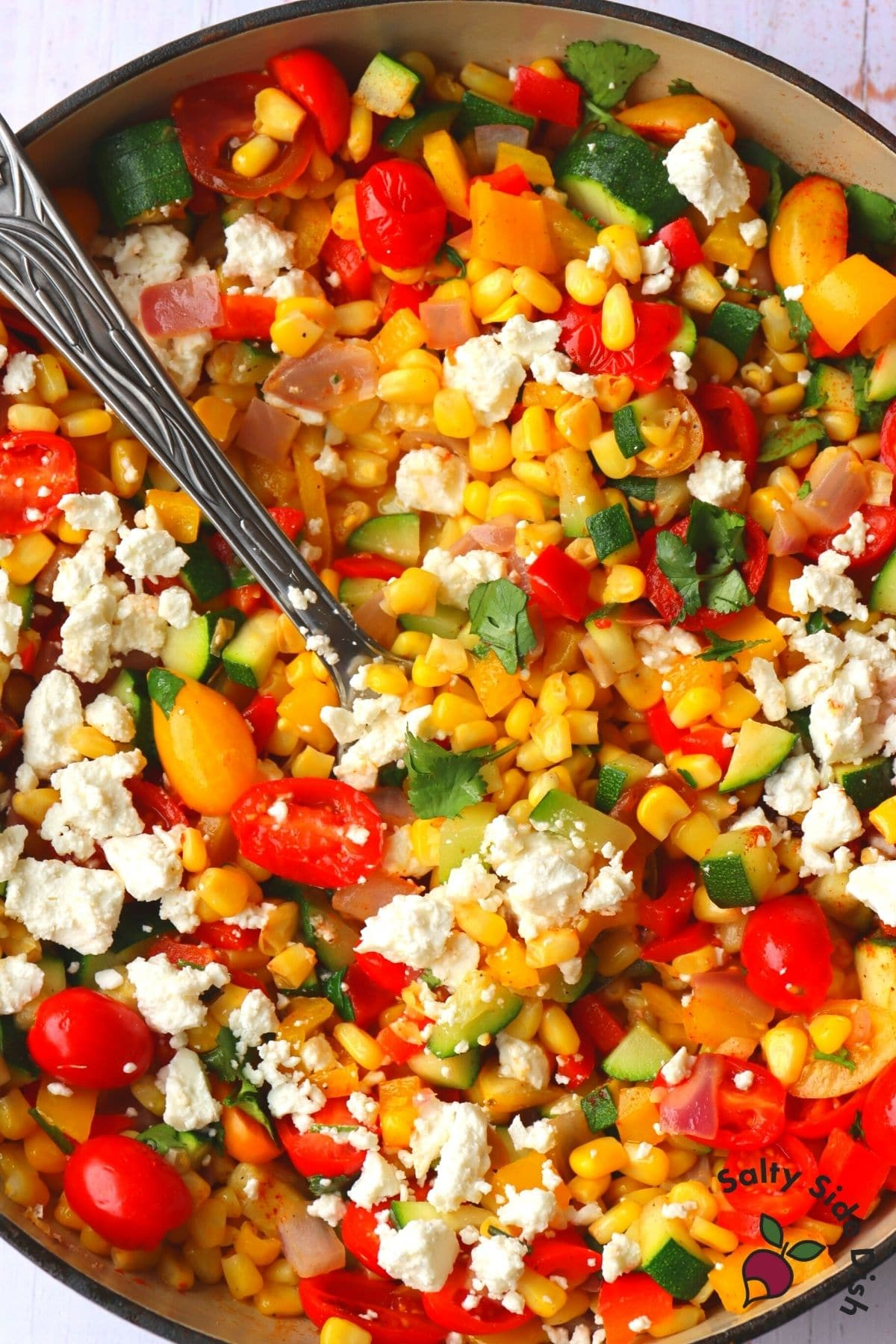 corn succotash in a skillet with a spoon