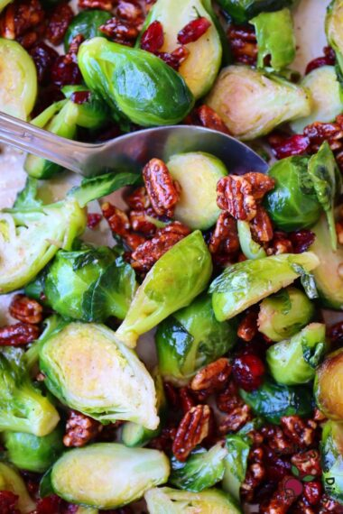 pecan brussels sprouts with cranberries being picked up by a spoon