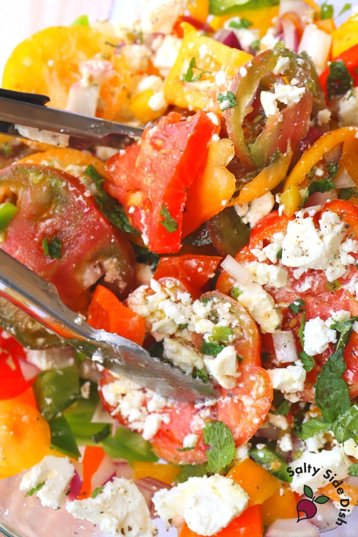 feta Greek tomato salad with tongs