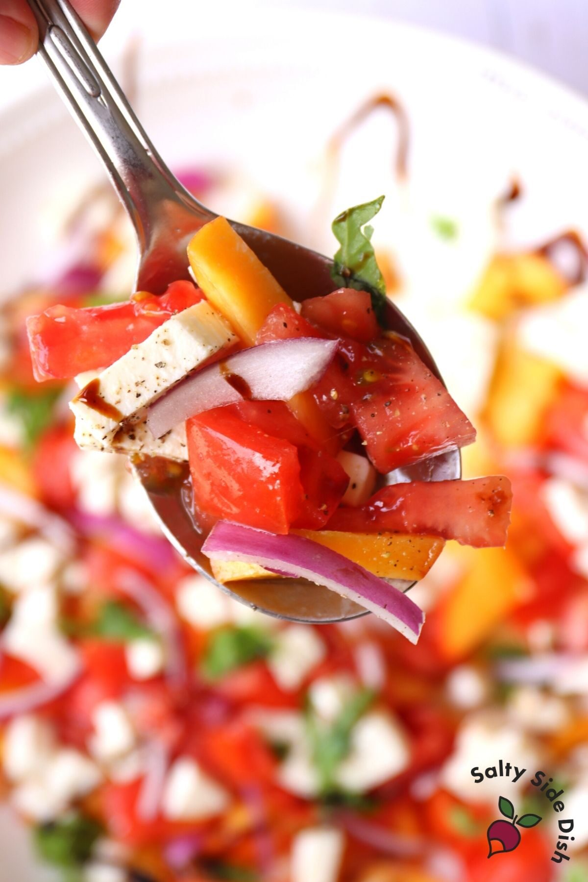 bite of caprese mozzarella salad with fresh peach slices and red onions on a spoon