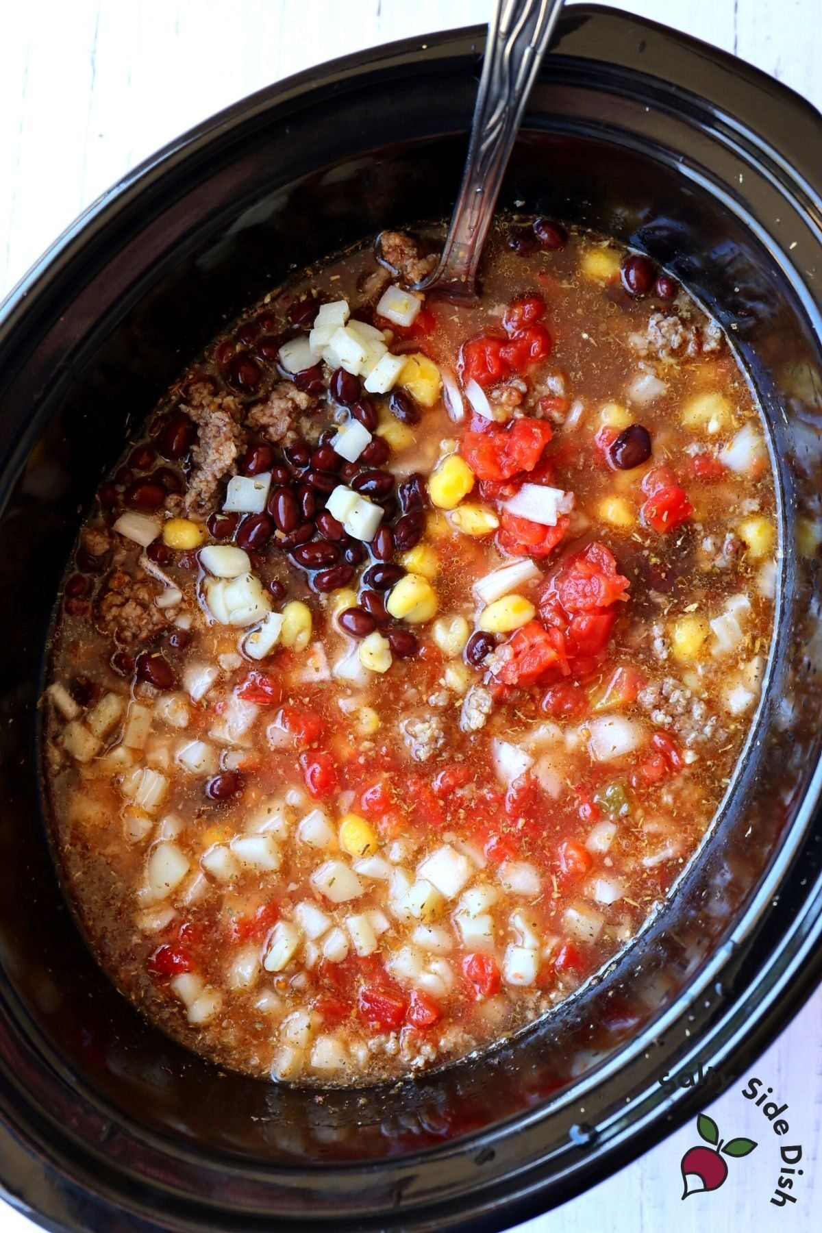 easy black bean soup in a slow cooker being stirred