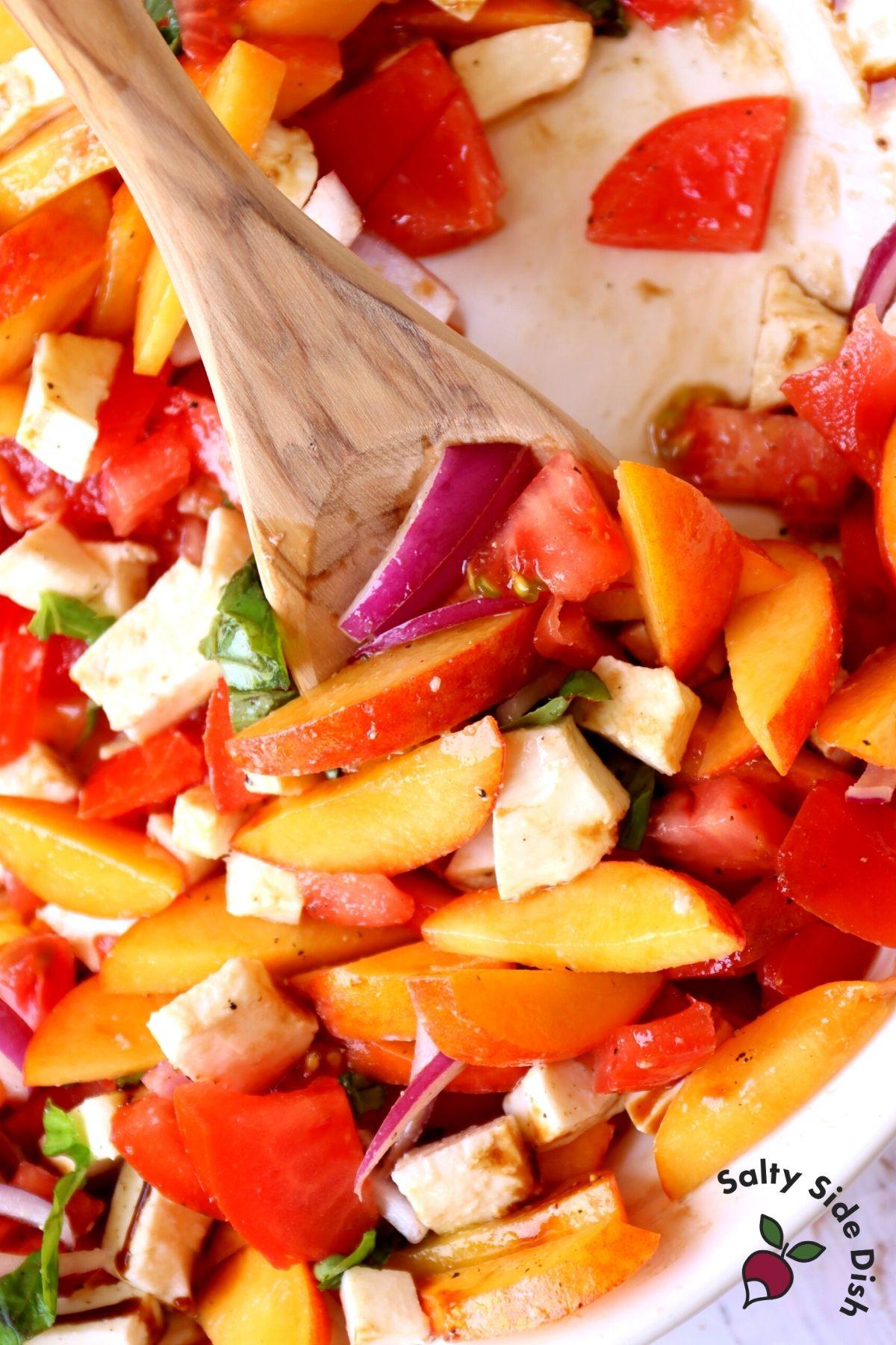 ripe summer peach salad in a bowl being stirred