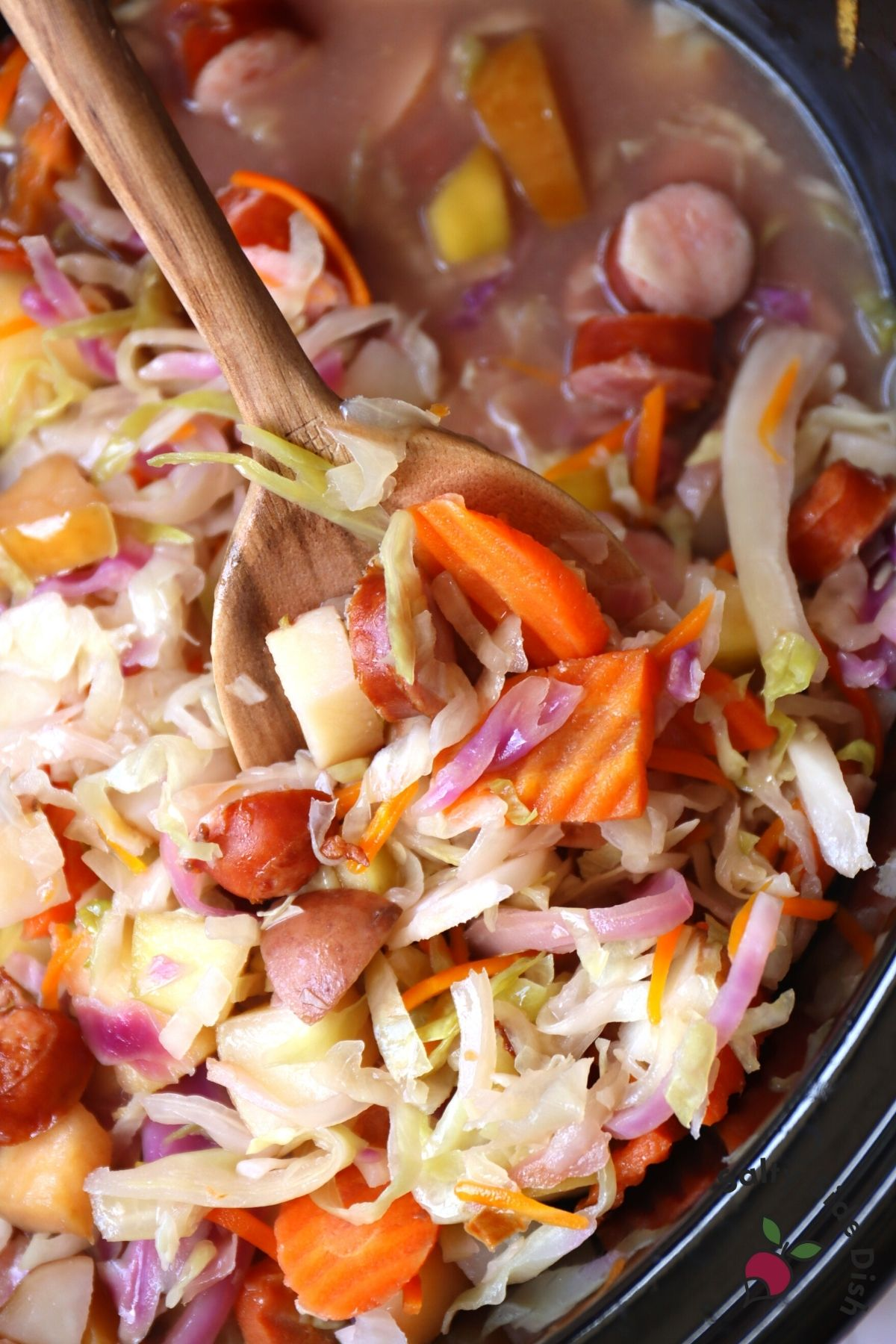 large slow cooker with sausage and cabbage stew on a wooden spoon
