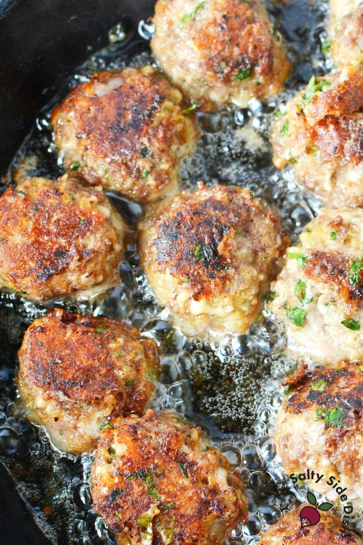 cast iron pan frying meatballs.