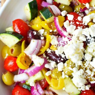 white plate with greek salad on top full of vegetables and feta cheese.