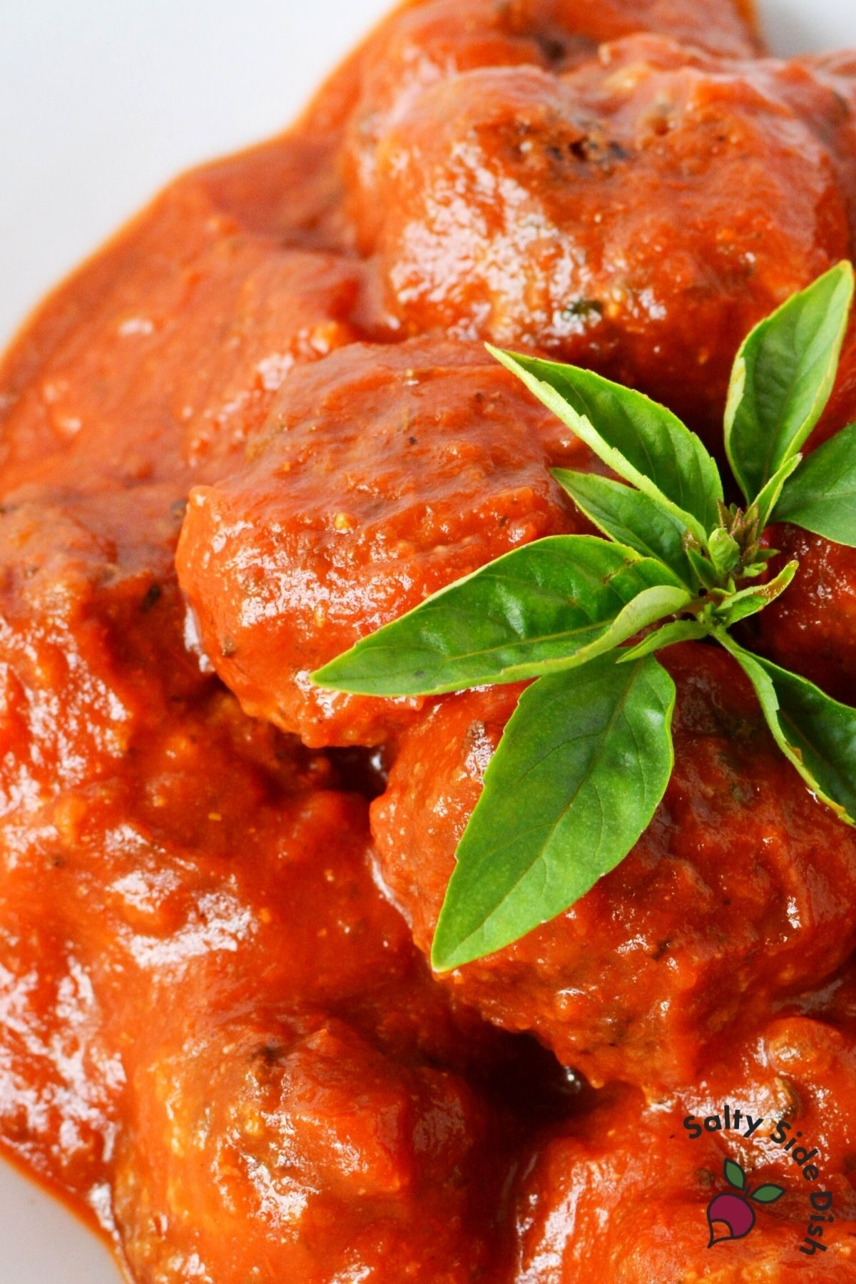 homemade meatballs with red sauce and dried herbs on top.