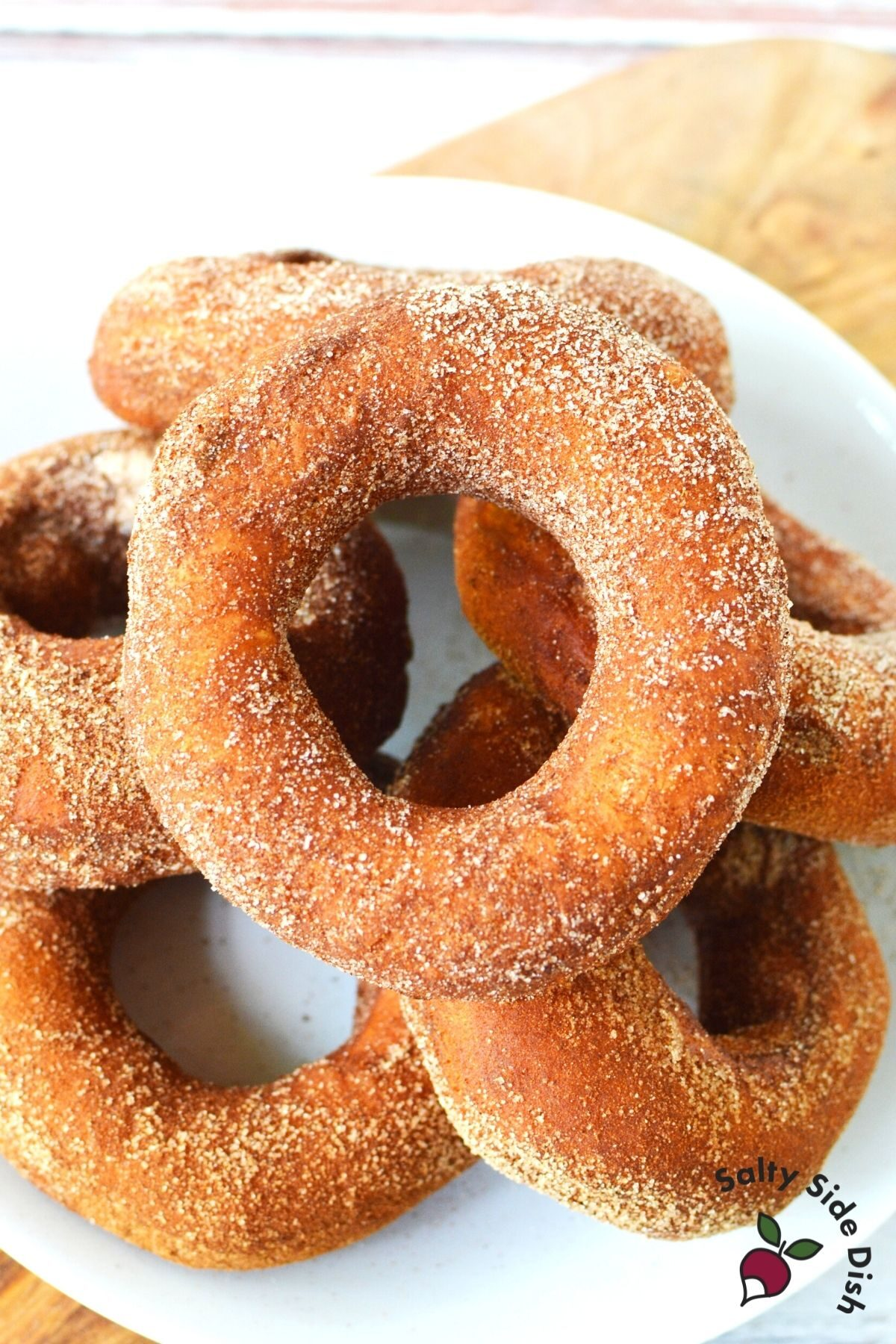 white plate piled high with cinnamon sugared donuts