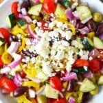 huge bowl of greek salad on a plate with feta cheese on top.
