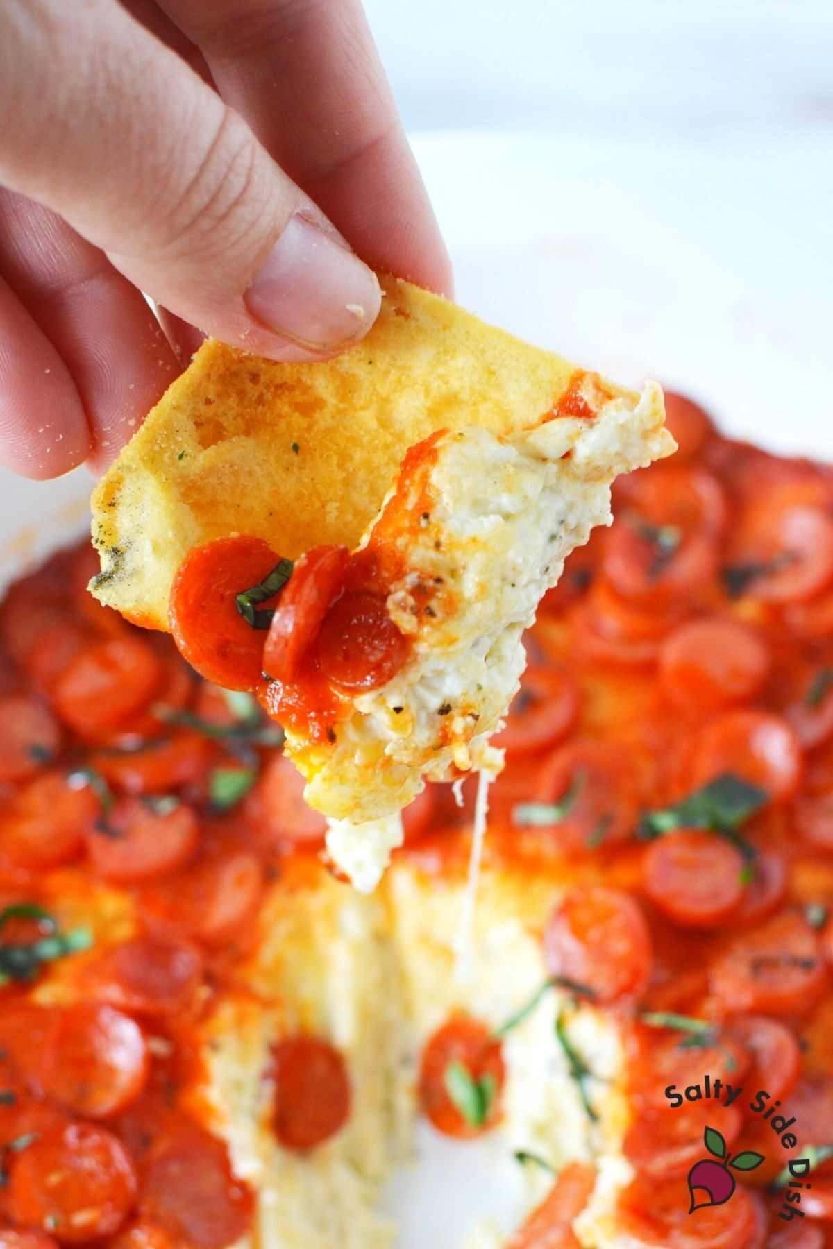 pita chip being dipped into and pulled out of pizza dip.