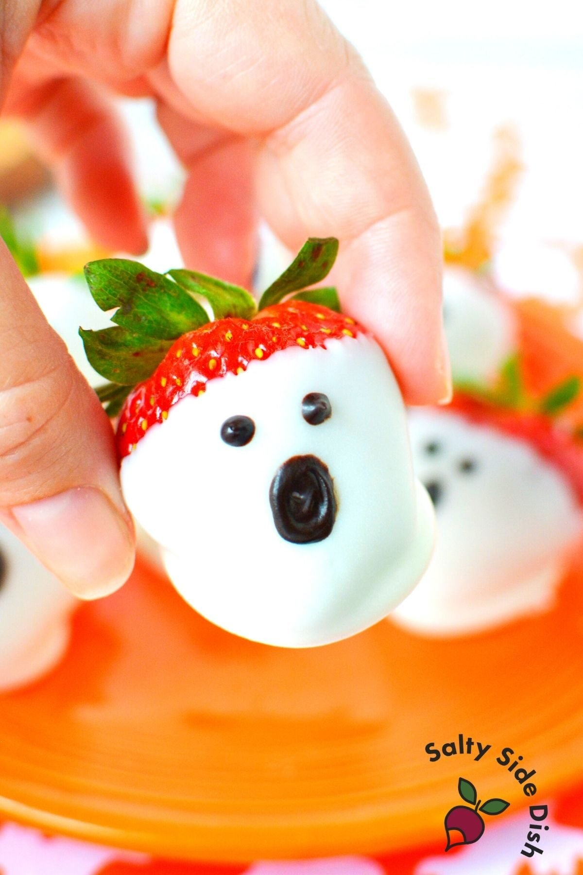 fingers holding a chocolate dipped strawberry that looks like a ghost with an orange plate in background.