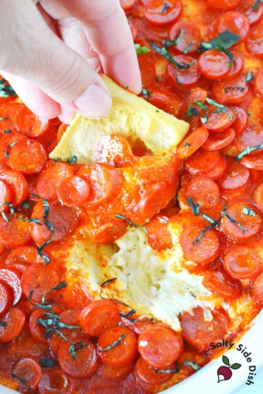 hand holding pita chip and dipping into pepperoni topped pizza dip.