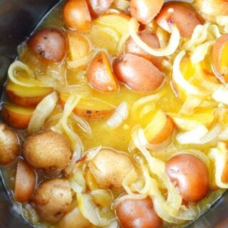 potatoes and onions in a black crockpot.