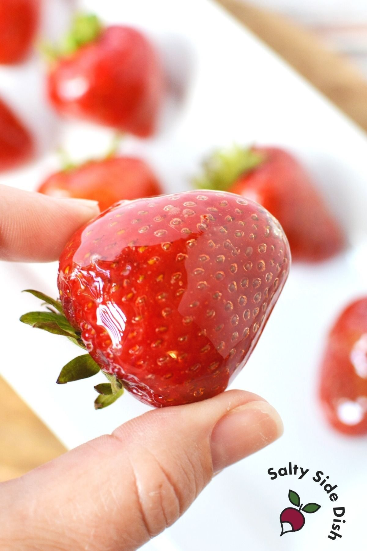 holding a tangulu candied strawberry with a finger and thumb.
