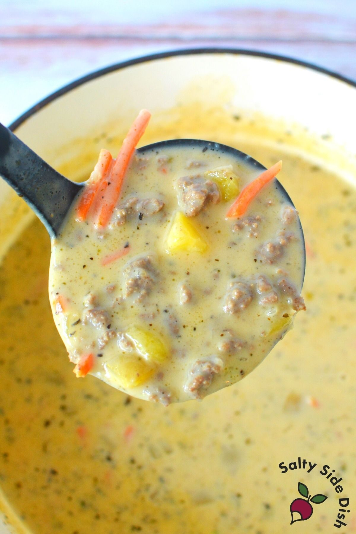 ladle dipping out a large scoop of creamy hamburger soup.