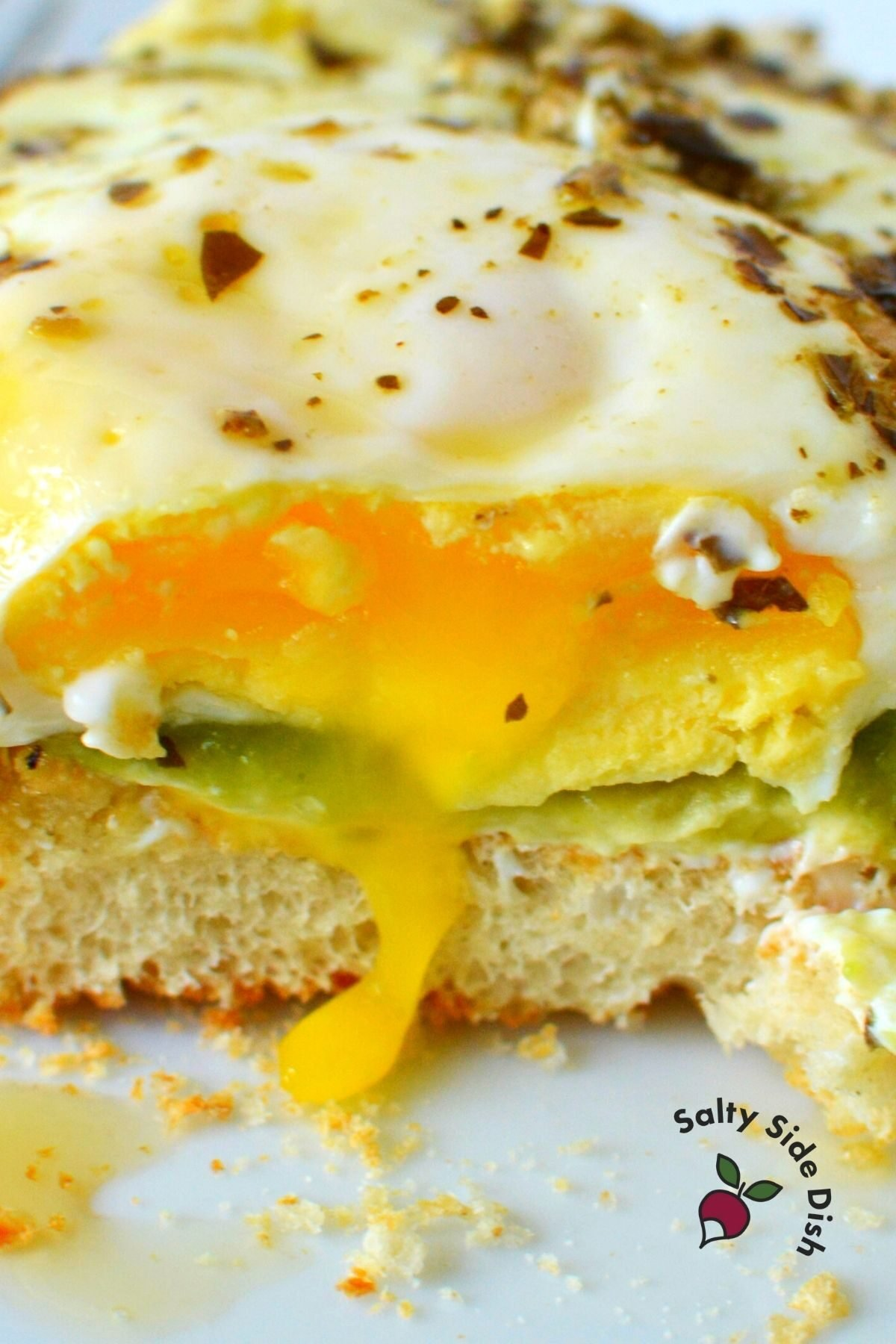 runny eggs on a sandwich with pesto and avocado.