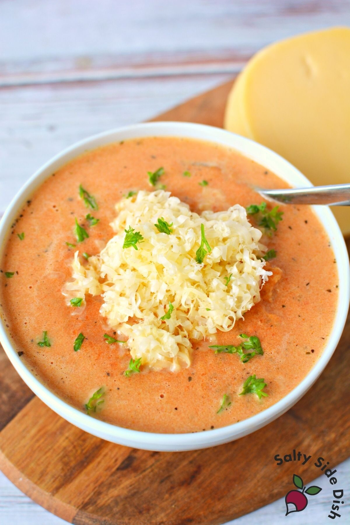 red pepper gouda soup in a white bowl.